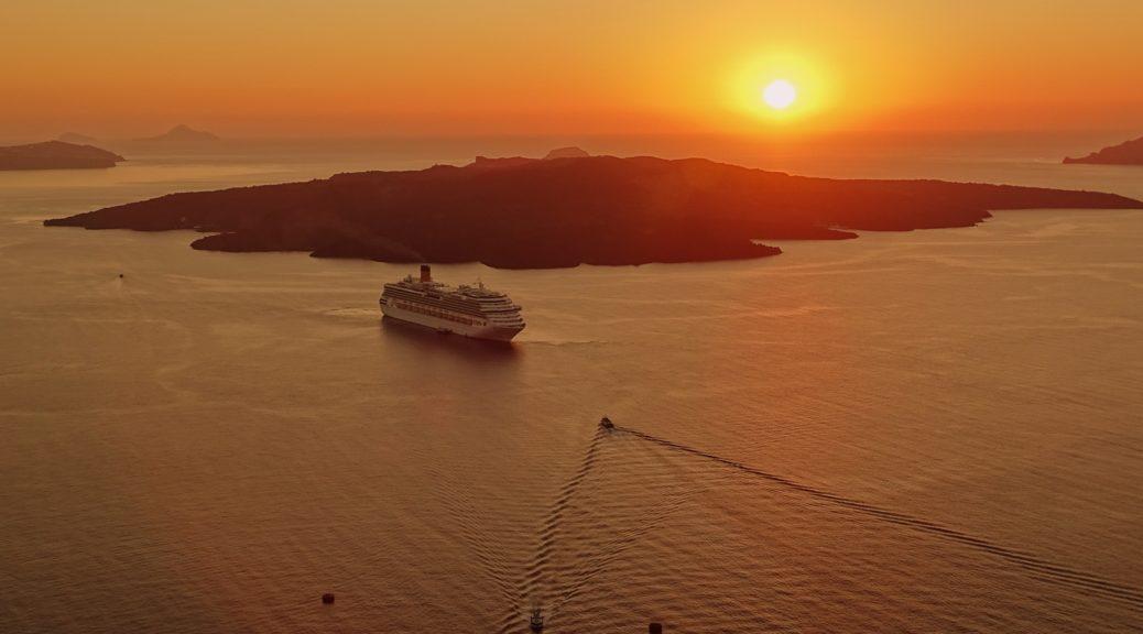 Vue au loin d'un bateau de croisière sur la mer, au coucher de soleil.