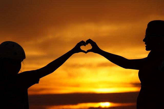 Deux enfants qui forment un cœur avec les mains devant la mer sur un bateau de croisière.